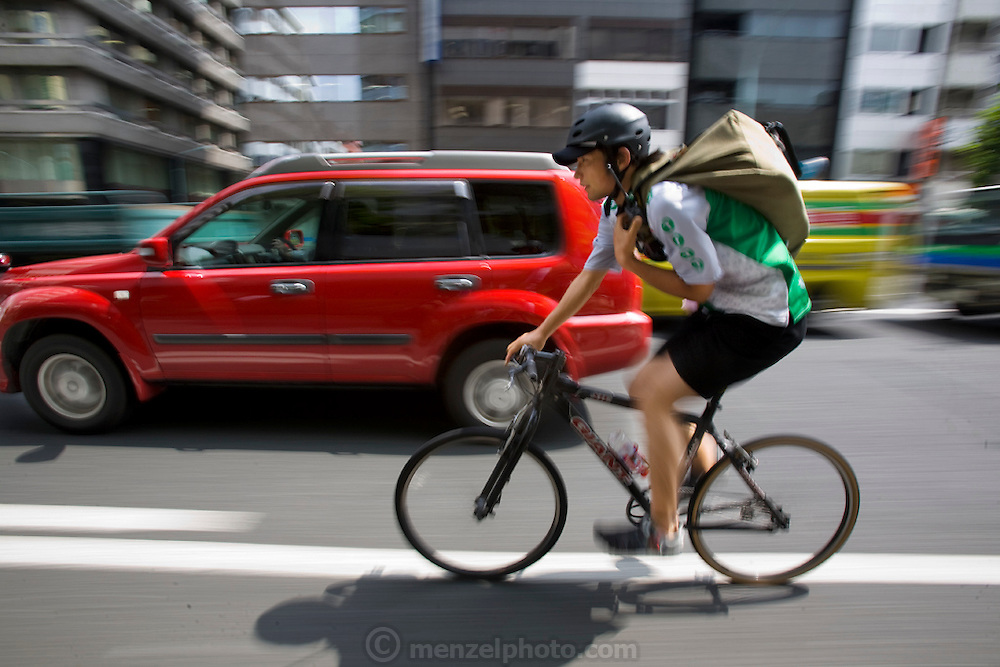 Jun Yajima, a messenger at T-Serv Bike Messenger service, powers through downtown Tokyo traffic to deliver a package suspended in his shoulder bag, while also keeping an ear out for his dispatcher to assign him his next pickup location. (From the book What I Eat: Around the World in 80 Diets.)  MODEL RELEASED.
