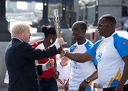 Image ©Licensed to i-Images Picture Agency. 06/06/2014. London, United Kingdom. Mayor of London welcomes Commonwealth Games Queen\'s Baton Relay to London with the World and Commonwealth champion Christine Ohuruogu MBE, Faramolu Johnson and Michael Pusey (carrying the baton) to the capital as part of the England led of a journey that will see it travel 190,000 kilometres over 288 days. City Hall, The Queen\'s Walk. Picture by Daniel Leal-Olivas / i-Images