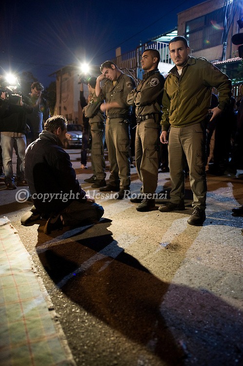 JERUSALEM: A Palestinian man knees to pray in front of Israel border policemen near a disputed house in Sheikh Jarrah neighborhood..© ALESSIO ROMENZI