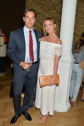 DAVID GIGAURI and MAGDALENA GABRIEL at a private view and auction of millinery organised by author, philanthropist and hat collector Eva Lanska in aid of Women for Women International held at Pace, Burlington Gardens, London on 10th June 2015.