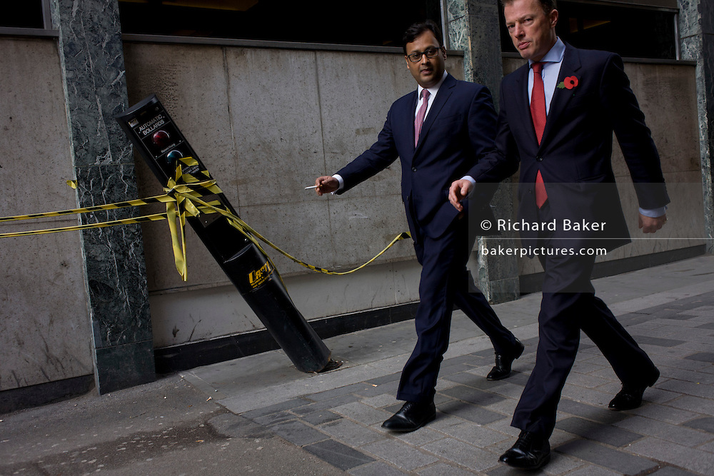 Businessmen walk past a leaning automatic traffic control bollard in St . Swithins Lane, City of London.