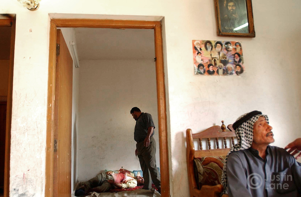 An Iraqi police officer stands over the body of a murdered man. A relative grieves in the foreground.