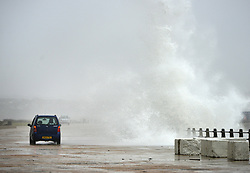© Licensed to London News Pictures. 15th January 2018. Newhaven, UK. Large waves crash over a car on the seafront at the port of Newhaven as strong winds across the South Coast whip up stormy weather in the English Channel. Photo credit: Peter Cripps/LNP