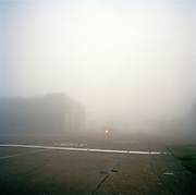 Old WW2 Dambusters hangar now belonging to the Red Arrows, Britain's RAF aerobatic team, airfield mist landscape.