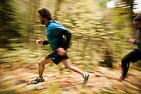 A high angle panning view of two men trail running in Fall colors.