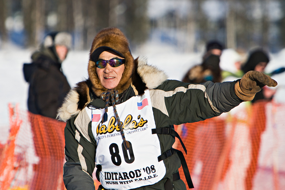 Musher Louis Nelson Sr. waves to the crowds as he leaves Willow Lake in Alaska at the start of the 2008 Iditarod on March 2, 2008.