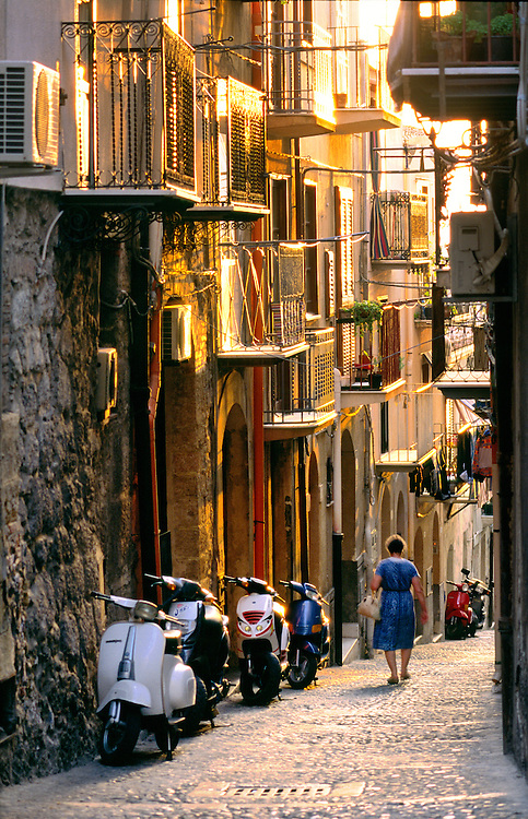 Cefalu, Sicily, Italy. Woman walks down cobbled street of coastal fishing resort town of Cefalu past scooters, mopeds. Evening