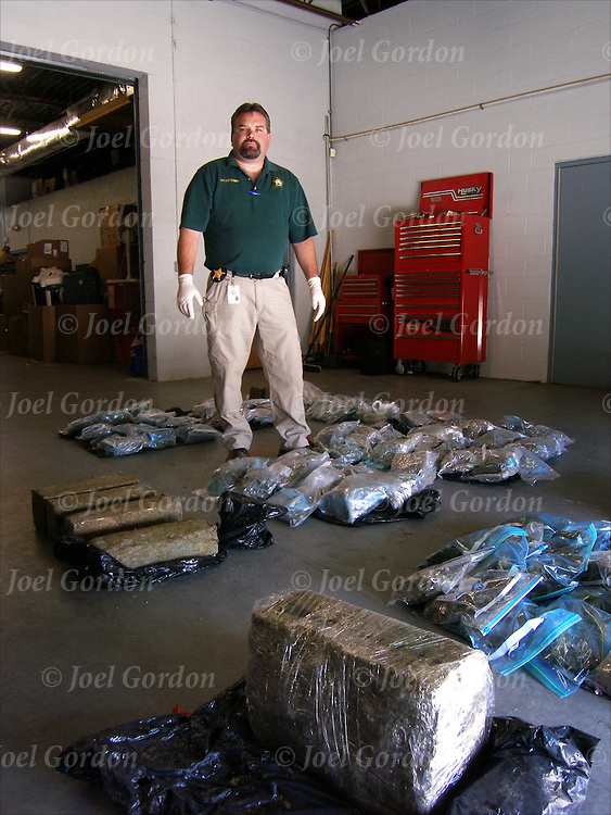 Dan Fleming, Crime Scene Investigator holding 9 lb. block of cannabis, in evident room in the Putnam County Sheriff?s Office, FL