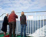 Three people looking back to the island from a Caledonian MacBrayne ferry ship leaving Barra, Outer Hebrides, Scotland, UK