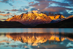 The majestic peaks and spires of Torres del Paine as they reflect on a calm lake at sunrise, Torres del Paine, Chile, South America