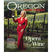 Opera singer Nancy Emrick singing and holding an Elk Cove Pinot Noir in the La Boheme vienyards at Elk Cove's winery at sunset for Oregon Wine Press.