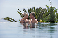 Mature couple drinking daiquiri in outdoor pool