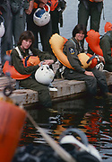 The first female NASA astronauts qualify in Water Survival School at Turkey Point, Florida. Here NASA astronaut candidates (left) Anna L. Fisher and (right) Sally Ride sit among their male classmates as they await their turn in a helicopter water pickup exercise.
