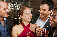 Two couples laughing holding drinks in bar