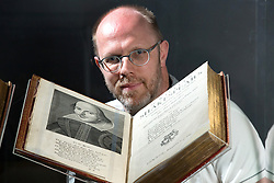 © Licensed to London News Pictures. 21/4/2016. Birmingham, UK. Rare and unseen Shakespeare items, including the first Folio are to go on display in a free exhibition at Birmingham Library from tomorrow. Pictured, Shakespeare Curator Julian Harrison with the first Folio, one of the main items in the exhibition. Photo credit : Dave Warren/LNP