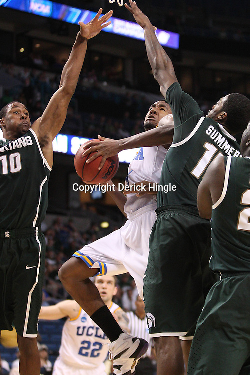 Mar 17, 2011; Tampa, FL, USA; UCLA Bruins guard Malcolm Lee (3) shoots between Michigan State Spartans defenders forward Delvon Roe (10) and guard Durrell Summers (15) during the second half of the second round of the 2011 NCAA men's basketball tournament at the St. Pete Times Forum. UCLA defeated Michigan State 78-76.  Mandatory Credit: Derick E. Hingle