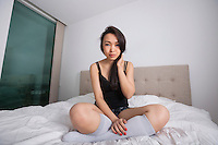 Full length portrait of beautiful young woman in sleepwear on bed