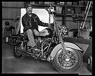 Joe Ackley sits on his Harley Davidson Heritage Softail for a portrait in his garage in Topeka, Kansas in December 2015.