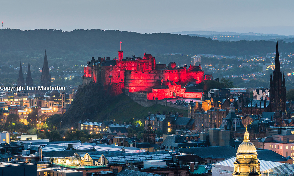 View of  Edinburgh Castle illuminated in red  in the evening from Salisbury Crags in Edinburgh, Scotland, United Kingdom.