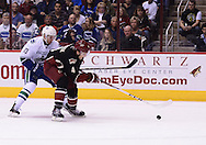 Nov 5, 2013; Glendale, AZ, USA; Phoenix Coyotes defensemen Zbynek Michalek (4) skates with the puke against the Vancouver Canucks forward Jeremy Welsh (13) in the first period at Jobing.com Arena. Mandatory Credit: Jennifer Stewart-USA TODAY Sports