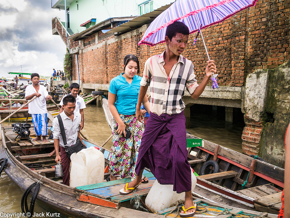 13 JUNE 2013 - YANGON, MYANMAR:   Commuters get off of cross river boat at the Aung Mingalar Jetty in Yangon. The jetty is a stop for commuters who live on the far side of the Irrawaddy River and ride small boats back and forth across the river. Yangon, formerly Rangoon, is Myanmar's commercial capital and used to be the national capital. The city is on the Irrawaddy River and has a vibrant riverfront.   PHOTO BY JACK KURTZ