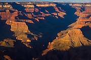 The late afternoon sun causes Bright Angel Canyon to fall into a deep shadow. Bright Angel Canyon is one of several tributary canyons that feed into the Grand Canyon. This image was captured from the Mather Point, located on the south rim of Grand Canyon National Park, Arizona.