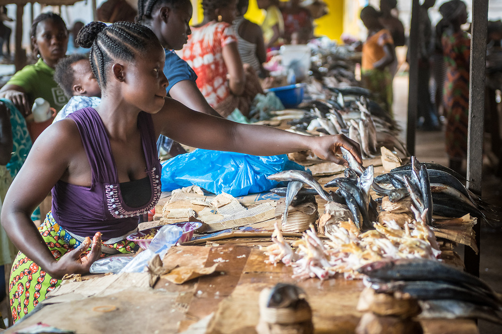 A woman looks at fish in the market in Ganta, Liberia