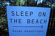 Sign that says 'sleep on the beach.' Quart festival, Kristiansands Norway 2000
