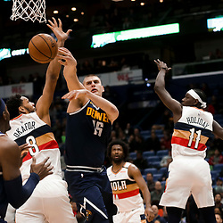 Jan 30, 2019; New Orleans, LA, USA; Denver Nuggets center Nikola Jokic (15) passes as he is defended by New Orleans Pelicans center Jahlil Okafor (8) and guard Jrue Holiday (11) during the second quarter at the Smoothie King Center. Mandatory Credit: Derick E. Hingle-USA TODAY Sports