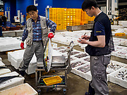 07 JUNE 2018 - SEOUL, SOUTH KOREA:  A vendor weighs a tuna before the wholesale auctions at the Noryangjin Fish Market. The auctions start about 01.00 AM and last until 05.00 AM. Noryangjin Fish Market is the largest fish market in Seoul and has been in operation since 1927. It opened in the current location in 1971 and was renovated in 2015. The market serves both retail and wholesale customers and has become a tourist attraction in recent years.      PHOTO BY JACK KURTZ