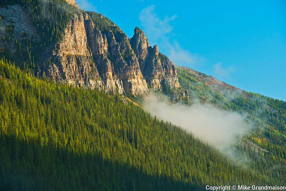Morning clouds swirling about Mt. Temple northeast of Moraine Lake at sunrise.<br />
