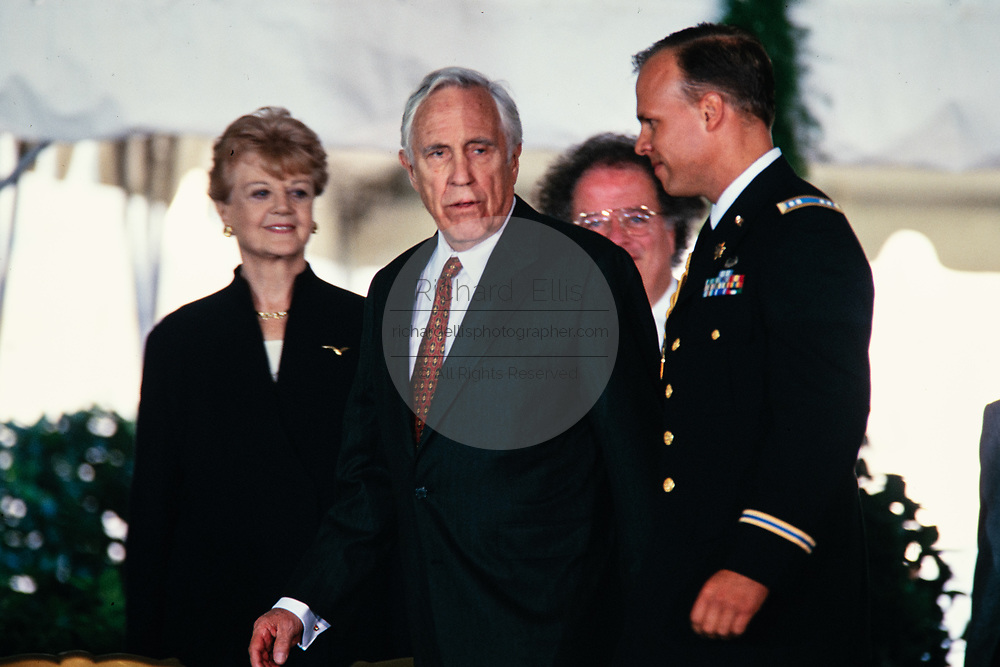 Actor Jason Robards is escorted back to his chair after being awarded the National Medal of Arts by President Bill Clinton and First Lady Hillary Clinton during a ceremony on the South Lawn of the White House September 29, 1997 in Washington, DC. Actress Angela Lansbury, left, and Music Director of the Metropolitan Opera James Levine look on.
