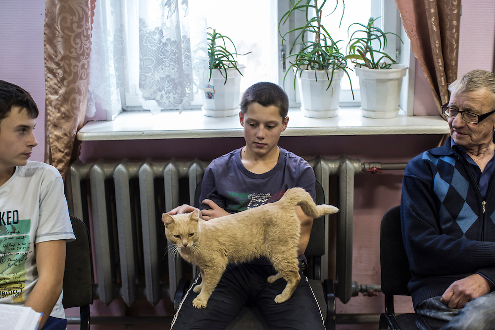 YEKATERINBURG, RUSSIA - OCTOBER 16: A boy who lives at a facility run by City Without Drugs for at-risk youth holds a cat that visits the house from time to time on October 16, 2013 in Yekaterinburg, Russia. Nine boys, many of whom were either experimenting with drugs or had dropped out of school, live at the group home, where school attendance and homework are mandatory. They are supervised day and night by Alexandr Fedorovich (R). City Without Drugs is a well-known narcotics treatment program in Russia founded by Yevgeny Roizman, who was elected mayor of Yekaterinburg in September 2013. (Photo by Brendan Hoffman/Getty Images) *** Local Caption *** Alexandr Fedorovich