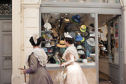 Passersby dressed with traditional costume of Arles in front of a milliner shop window, Arles, France, July 3, 2016. <br /> Passanti in costume tradizionale di fronte ad un negozio di modista ad Arles, Francia, 3 luglio 2016.