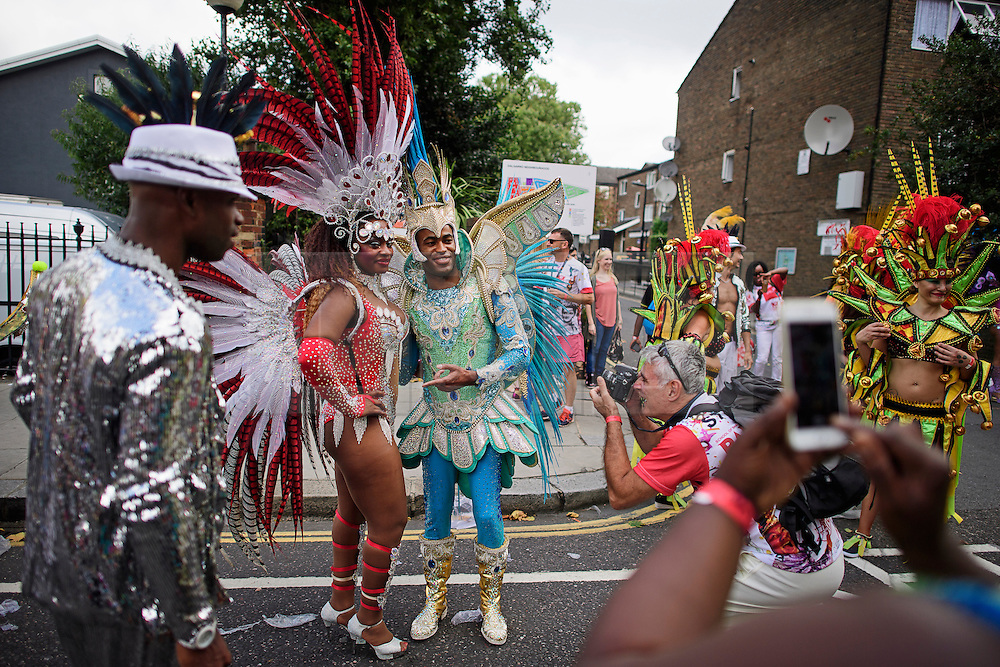 © Licensed to London News Pictures. 29/08/2016. London, UK. Carnival goers in costume have their picture taken while waiting to take part in  day two of the Notting Hill carnival, the second largest street festival in the world after the Rio Carnival in Brazil, attracting over 1 million people to the streets of West London.  Photo credit: Ben Cawthra/LNP