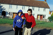 Two kids standing outside some houses, one wearing a hoodie