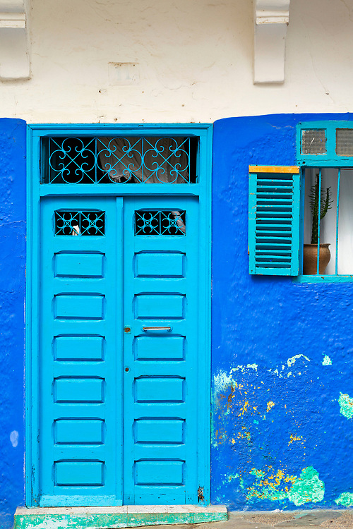 Moroccan door architecture, Asilah, Northern Morocco, 2015-08-10.<br /><br />Asilah is a sleepy fishing town in the North of Morocco, just one hour south of Tangier. While not completely off Morocco's well-beaten path, it's often missed by travellers bound inland for Fez or Chefchaouen, yet has a uniquely alluring charm. With an immaculately restored medina that's re-painted vivid shades of blue & white each summer, Asilah has the feel of being Morocco's own Santorini - a great spot to see the more chilled out, seaside town life in Morocco.  <br /><br />The architecture in Asilah has been heavily influenced by these different periods of occupation, which is one of the main reasons for its unique and characterful feel. Evidence of Mediterranean design can be seen in the rampart walls and gates themselves, reflecting the Spanish & Portuguese influence on the Asilah's development, Roman ruins can be found in the nearby town of Larache and Arab influences are more subtly found in the decorative window shutters and the labyrinth like medina layout to the streets. <br /><br />If a lover of the quirkier details found in the medinas of Morocco, then Asilah won't disappoint, with hundreds of creatively designed doorways, decorative window shutters and retro, old electricity & water metres from the French occupational period. Together with the art work and murals spread throughout the medina, these little details all paint the picture of Asilah. One of the main things to do is to simply wander the streets and take in all the unusual textures, shades & charm the town has to offer.