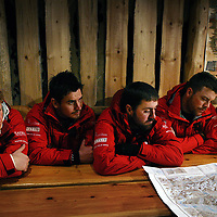 Prince Harry looks at maps with his team on their way to the North Pole.Photograph David Cheskin.