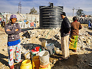 04 MARCH 2017 - KATHMANDU, NEPAL: People who bought water for the tank near their tents line up for water in an IDP camp in the center of Kathmandu. This tank is filled with water residents purchase. The city is no longer providing free water to the camp. The camp opened days after the April 2015 earthquake devastated Nepal, killing almost 9,000 people. At its peak, about 1,800 families lived in the camp. The camp is still open nearly two years after the earthquake, about 400 families currently live in the camp. Camp residents say the Kathmandu municipal government is trying to close the camp and is encouraging residents to find new housing. They said the government is cutting off services to the camp and last week stopped the free distribution of water, although water can be purchased for delivery. Most of the people in the camp came to Kathmandu from rural villages in the mountains in the weeks after the earthquake. Many of the residents of the camp, technically homeless, have found work in Kathmandu's bustling construction industry, rebuilding homes destroyed in the earthquake.       PHOTO BY JACK KURTZ