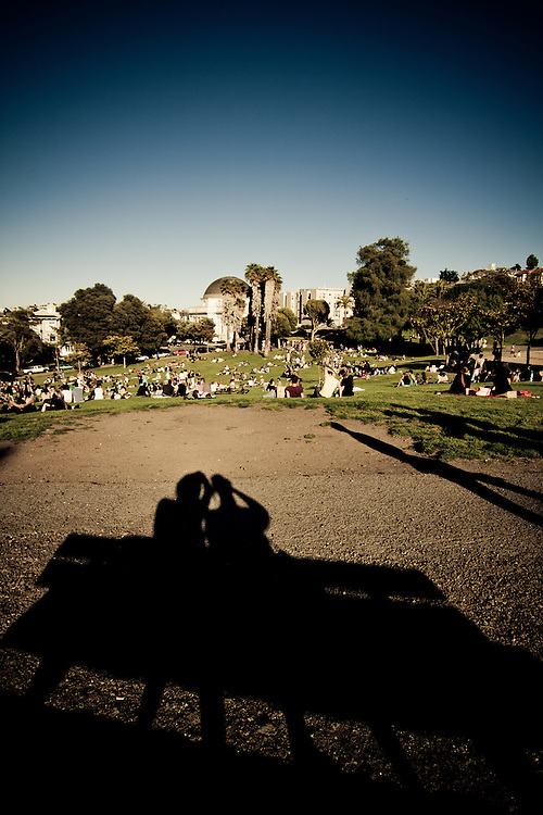 A shadow of two people taking a picture from a bench in Dolores Park, San Francisco, California, USA.