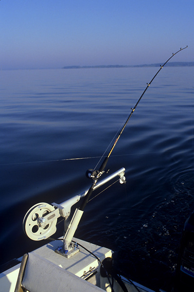 Stock photo of a rod secured to the back of a boat and trolling for fish