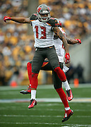 Tampa Bay Buccaneers wide receiver Mike Evans (13) leaps and celebrates with a hip bump with Tampa Bay Buccaneers wide receiver Louis Murphy (18) after Evans catches a first quarter touchdown pass for a 7-0 Bucs lead during the NFL week 4 regular season football game against the Pittsburgh Steelers on Sunday, Sept. 28, 2014 in Pittsburgh. The Bucs won the game 27-24. ©Paul Anthony Spinelli