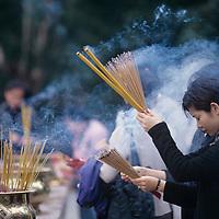 Hong Kong, Woman burns incense at Wong Tai Sin Taoist Temple in Kowloon