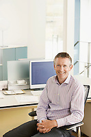 Middle-aged male office worker sitting in cubicle portrait