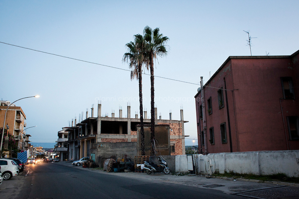 Rosarno, Italy - 31 August, 2012:  Two palms overlook an unfinished building in the main street of Rosano, Italy, a mafia stronghold on August 31, 2012. The unfinished concrete buildings, which are very common throughout Calabria, are the result of the inability to go beyond the merely useful, creating functionality without regard for form.<br /> <br /> <br /> Rosarno is an agricultural area best known for the violent race riots that erupted here in January 2010. and for being a hotbed of the 'Ndrangheta, a Mafia-type criminal organisation based in Calabria. The local 'Ndrangheta dominates the fruit and vegetable businesses in the area, according to Francesco Forgione, a former head of Italy's parliamentary Antimafia Commission. In December 2008, the entire town council was dissolved on orders from the central government and replaced by a prefectoral commissioner because it had been infiltrated by 'Ndrangheta members and their known associates.<br /> <br /> Calabria is one of the poorest Italian regions which suffers from lack of basic services (hospitals without proper equipment, irregular electricity and water), the product of disparate political interests vying for power. The region is dominated by the 'Ndrangheta (pronounced en-Drang-get-A), which authorities say is the most powerful in Italy because it is the welthiest and best organized.<br /> <br /> The region today has nearly 20 percent unemployment, 40 percent youth unemployment and among the lowest female unemployment and broadband Internet levels in Italy. Business suffer since poor infrastructure drives up transport costs.<br /> <br /> Last summer the European Union's anti-fraud office demanded that Italy redirect 380 million euros in structural funding away from the A3 Salerno - Reggio Calabria highway after finding widespread evidence of corruption in the bidding processes.