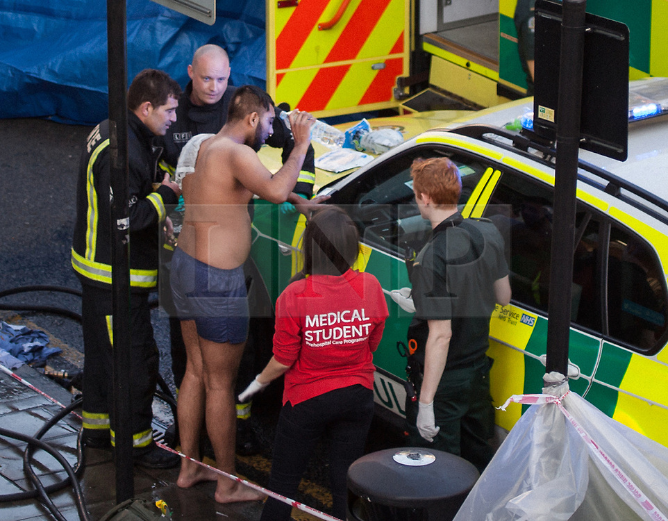 © Licensed to London News Pictures. 25/07/2017. London, UK. A victim of what is thought to have been an acid attack, is treated by emergency services on the side of the road in Bethnal Green. Two men have been taken to hospital after flagging down police for help. Photo credit: Liam Creighton/LNP