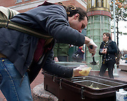 """November 3, 2010 - Brandon Bowser pours a bowl of vegetable soup, prepared by members of Food Not Bombs, for a man in Central Square in Cambridge on Sunday. The organization provides a free regularly scheduled vegan meal to anyone once a week in Cambridge. Visitors to the meal were scarce according to Food Not Bombs, """"usually we have people line up,"""" Bowser said. Photo by Lathan Goumas."""