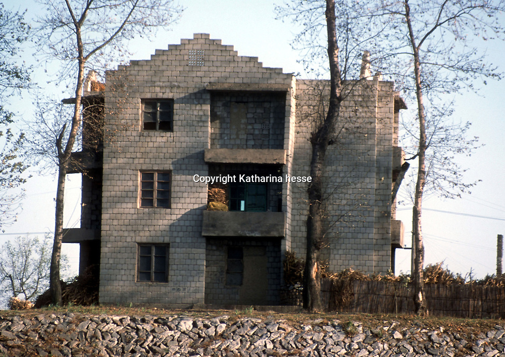 """CHINA, NORTH KOREAN  BORDER- OCTOBER 22: A house that appears to have no windows or heat is seen October 22, 2002 on the Sinuiju coast in North Korea on the Sino-North Korean border. North Korean nationals fleeing starvation or even sometimes imprisonment, usually are refused entry to China, and if caught, forcibly repatriated. Although China signed a treaty, the Chinese government considers the refugees as """"economic migrants,"""" and rejects arguments that the North Koreans are fleeing a repressive government whose policies have caused millions to die. Despite this official policy, however, in the frozen woods and rivers that separate China and North Korea, in recent years thousands have snuck across to freedom, helped by aid workers and sympathetic locals. Refugees as well as those who help them keep a low profile and remain anonymous"""