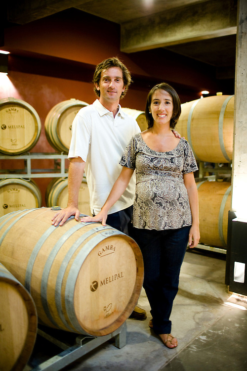 Husband and wife team Santiago Santamaria (left) and Clarisa Aristi, of Bodega Melipal, stand in amonst oak casks at the winery in the Luján de Cuyo area of Mendoza, Argentina.