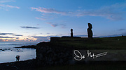 Tourists take photographs of the carved statues known as Moai stand with their backs to the sea, at Ahu Tahai on Easter Island, Chile.